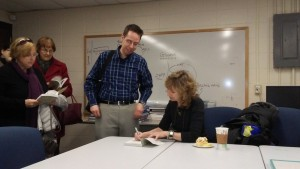 Many audience members stayed after the presentation to have their book signed by the author, including NECC professor Mike Cross