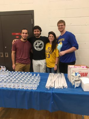 students behind a table serving concessions