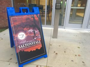 A sign promoting a play. The sign has a picture of a deep red sky and a noose
