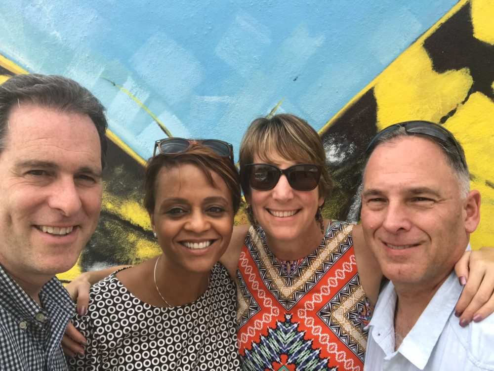Six NECC staff members standing together in PR. There is a yellow pice of cloth with black stripes standing behind them