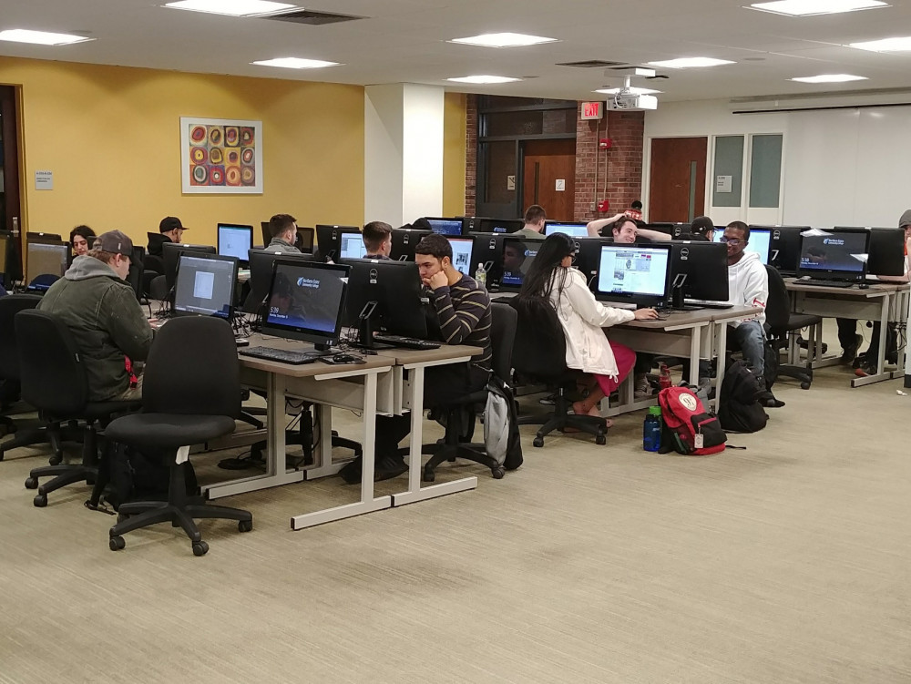 photo of rows of computers, and students doing work on them