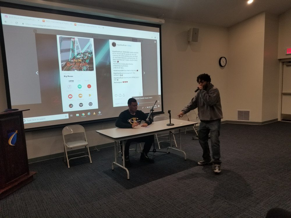student holding a mic raping in front of a projected screen