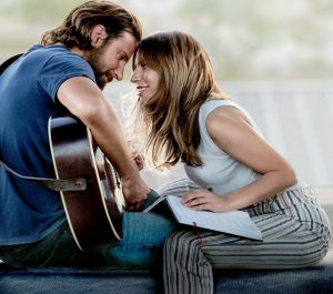 A man playing a guitar and a women leaning close to him