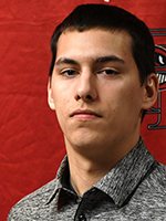 Photo of Evan Glew, in front of a red background.