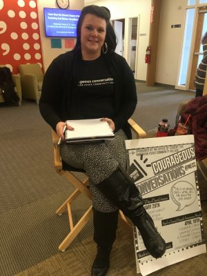 women siting in a directors style chair holding a notebook