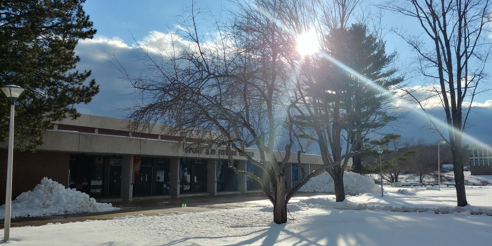 Photo of the outside of the fitness center. Ground has a thin layer of snow. Thare are two trees with no leaves in front of the building.