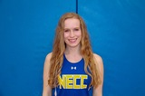 woman standing in front of blue background. She is wearing a necc sports uniform