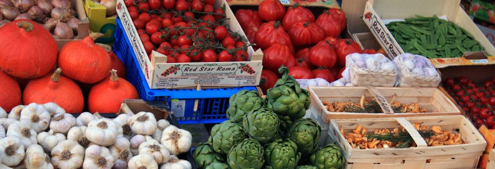boxes of fruits and vegetables at a farmers market
