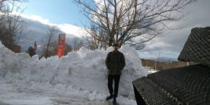 Photo of the editor in chef, Brennan Cooney standing in front of a mound of snow.