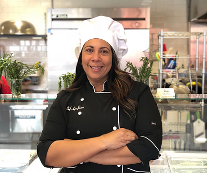close up picture of woman in chef uniform standing in kitchen