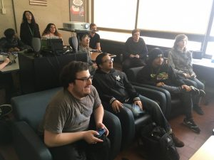 Several people siting holding controllers. Thare is a group in the front citing on two couches, and another group in the back standing