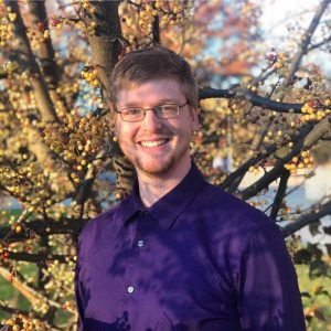 Man wearing purple button up shirt, standing outside in front of a tree.