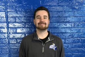 man standing in front of blue brick wall. He is wearing a black necc jacket