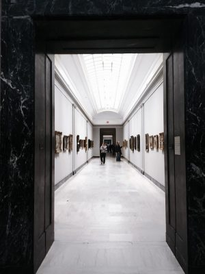 long brightly lit white hallway with paintings on ether side.
