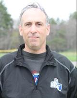 Profile shot of Nelson Desilvestre, standing outside wearing a NECC sports jacket