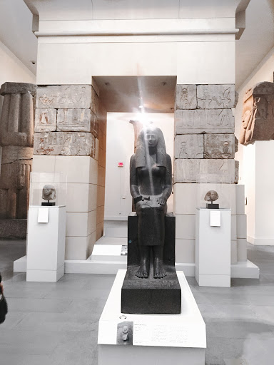 black statue of a pharaoh in a museum