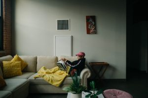 Josselyn Fernandez reading on her couch in her apartment